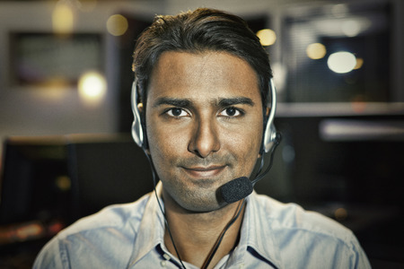 collared shirt: Man with headset smiling at the camera