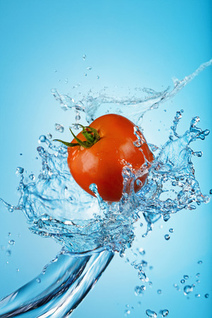 Tomato with splashing water against a blue background Stock Photo