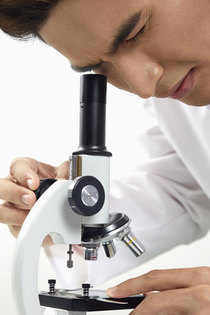 looking through: Lab personnel looking through a microscope