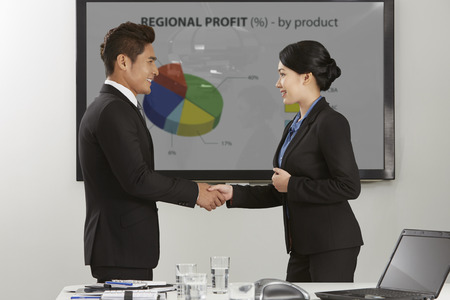 courteous: Businessman and businesswoman shaking hands