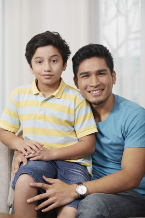 pre adolescent boy: Father and son smiling at the camera