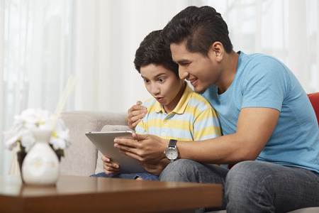 Father and son using a digital tablet together Banque d'images