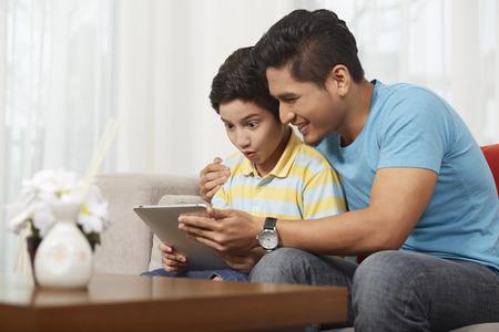 Vater und Sohn, die eine digitale Tablette zusammen
