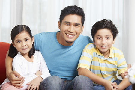 pre adolescent boy: Father and children smiling at the camera LANG_EVOIMAGES