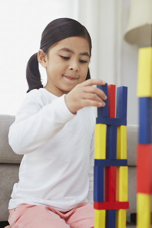 Girl playing with colorful building blocks
