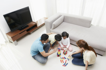 pre adolescent boys: Family of four playing with building blocks