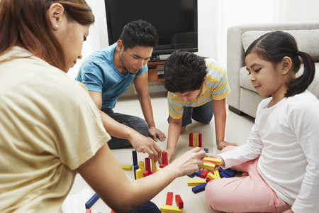 pre adolescent boy: Family of four playing with building blocks