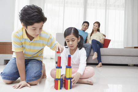 Boy and girl playing with blocks as parents look on