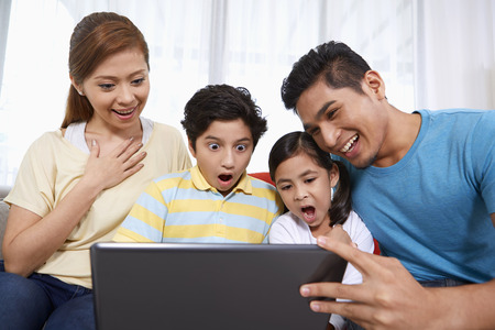 pre adolescent boy: Family of four sitting and using laptop together