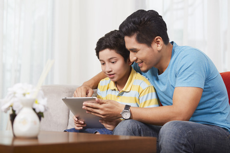 pre adolescent boy: Father and son using a digital tablet together LANG_EVOIMAGES