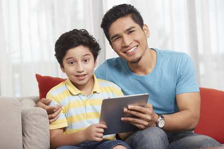 pre adolescent boys: Father and son using a digital tablet together LANG_EVOIMAGES