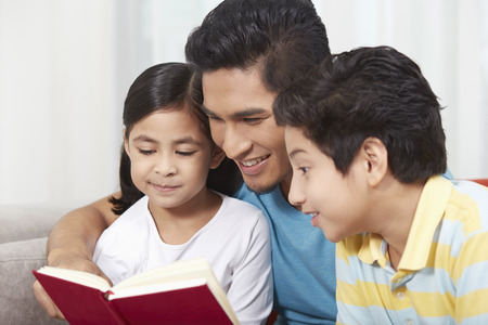 pre adolescent boys: Father reading a book with his children