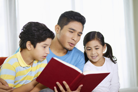 pre adolescent boy: Father reading a book with his children