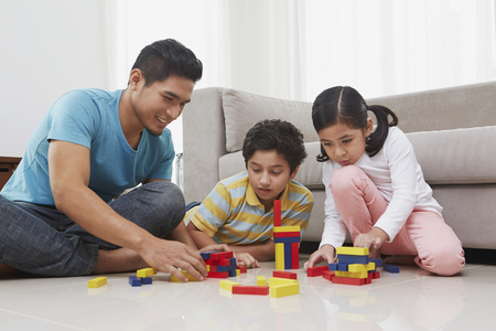 Cheerful father playing with his children Stock Photo