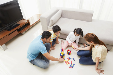 Family of four playing with building blocks
