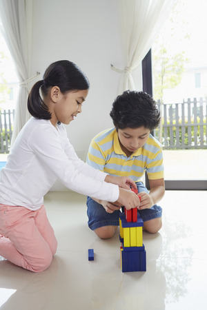 pre adolescent boy: Boy and girl playing with building blocks together