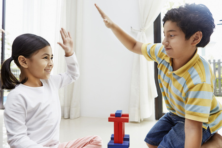 pre adolescent boy: Boy and girl giving each other a high five