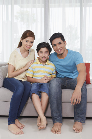 pre adolescent boy: Family of three smiling at the camera