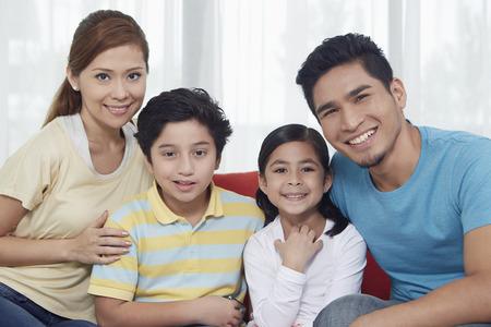 Vierköpfige Familie, fröhlich lächelnd in die Kamera