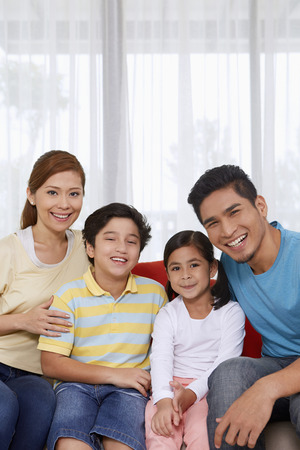 pre adolescent boy: Family of four cheerfully smiling at the camera LANG_EVOIMAGES