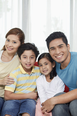 Family of four cheerfully smiling at the camera Stock Photo