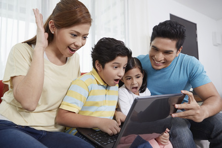 Family of four sitting and using laptop together
