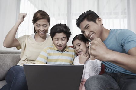 pre adolescent boys: Family of four sitting and using laptop together