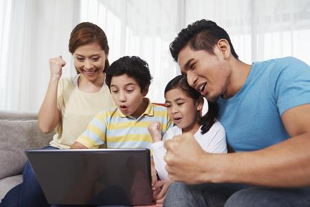 Familie von vier sitzen und mit Laptop zusammen