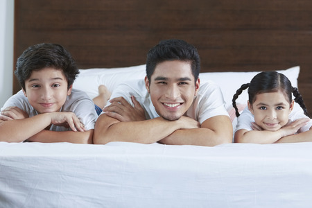 pre adolescent boy: Cheerful family smiling at the camera LANG_EVOIMAGES
