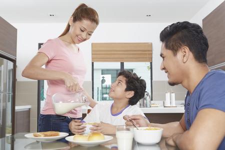 comiendo cereal: Madre verter la leche en un taz�n de hijo