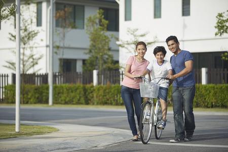 apoyo familiar: Los padres hijo ense�ando a montar en bicicleta