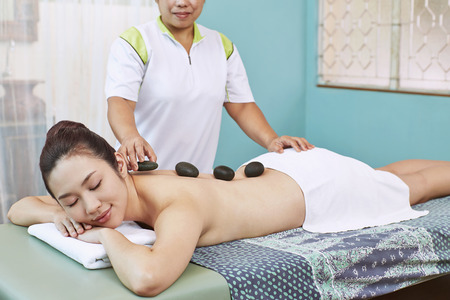 massage stone: Massage stone on a young womans back LANG_EVOIMAGES