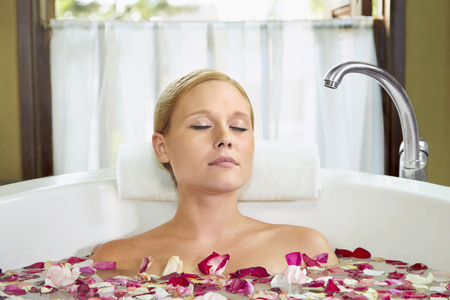 woman in bath: A young woman having a flower bath