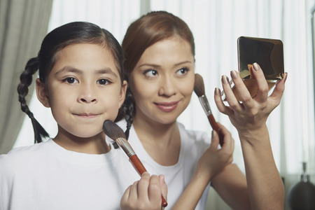 applying makeup: Mother and daughter applying makeup on face LANG_EVOIMAGES