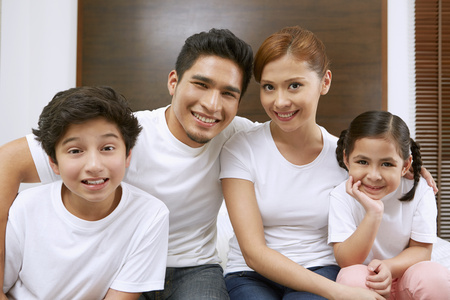 pre adolescent boy: Family of four smiling at the camera LANG_EVOIMAGES
