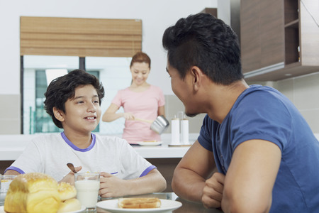 pre adolescent boy: Father and son having breakfast together