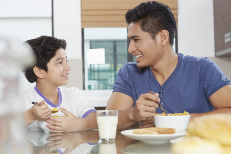pre adolescent boys: Father and son eating cereals