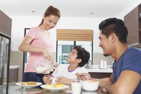 familia cenando: Madre verter la leche en un tazón de hijo