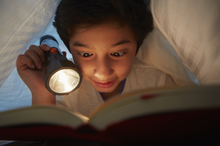 pre adolescent boy: Boy reading book under blanket with a torch light