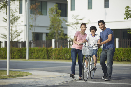 Parents teaching son how to ride a bicycle