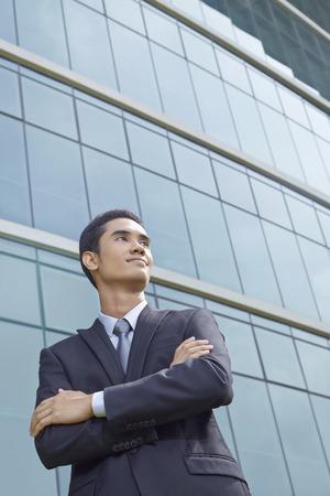 folding arms: Cheerful businessman thinking