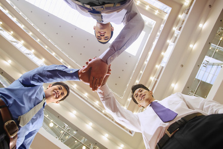 huddle: Businessmen having a team huddle LANG_EVOIMAGES