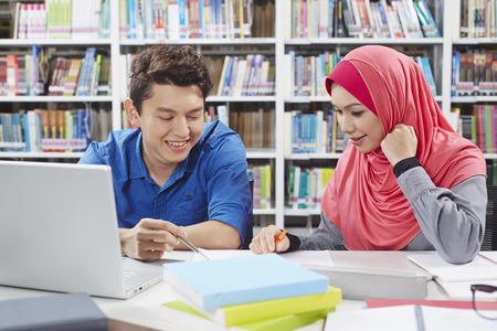 alumnos estudiando: Dos estudiantes que estudian juntos en la biblioteca LANG_EVOIMAGES