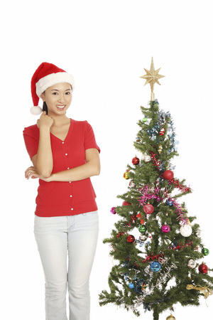 Young woman with christmas hat standing in front of christmas tree
