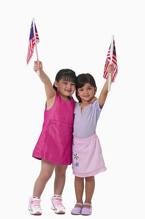 Jonge Maleisische en Chinese meiden die Maleisische vlag houden Stockfoto