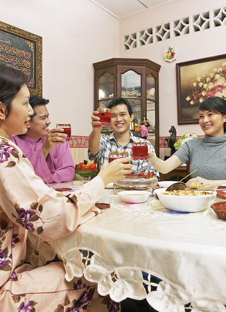 Guests enjoying feast on Hari Raya open house Banco de Imagens