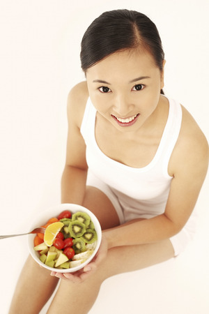 Woman enjoying a fruit and vegetable salad Stock Photo