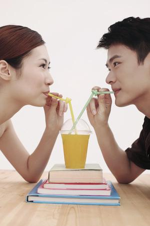남자와 여자는 오렌지 주스 한 잔 공유 스톡 콘텐츠