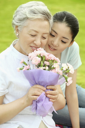 Senior woman and woman smelling bouquet of flowers