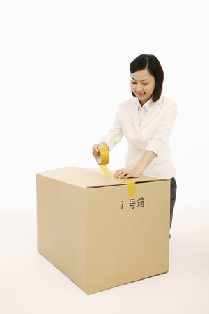 Businesswoman sealing cardboard box with tape